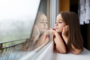 little girl looking out of a window